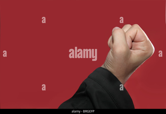 Male Caucasian hand clenched in anger against a red background - Stock Image