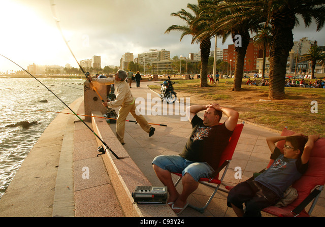 People fishing and walking along the Rambla, the city's riverfront promenade, Montevideo, Uruguay. - Stock Image