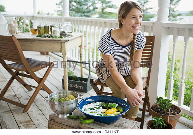 Woman washing vegetables on porch - Stock Image