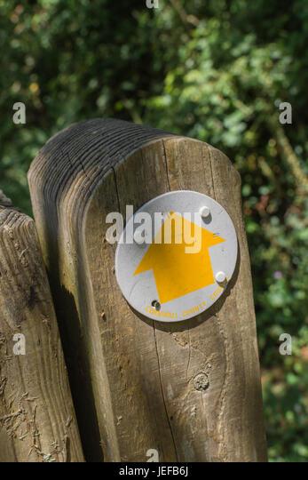 Yellow arrow marking countryside walk. - Stock Image