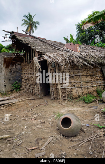 An old clay pot sits on the ground in front of an incomplete wattle and daub house in a remote stormy jungle village - Stock Image