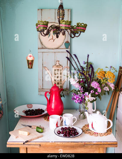 beaded chandelier above small table laid with summer picnic and wild flowers - Stock Image