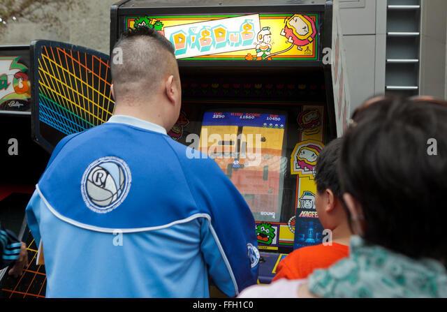 Young man playing Dig Dug arcade video game - USA - Stock Image