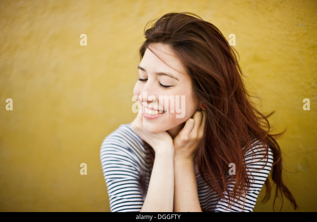 Candid portrait of young woman with eyes closed - Stock Image