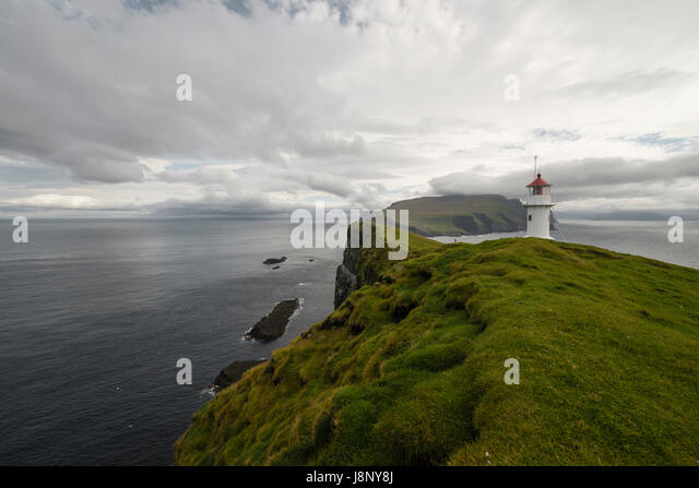 Lighthouse by sea on cloudy day - Stock-Bilder