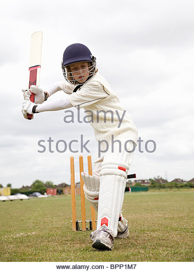 Boy (10-12) playing cricket - Stock Image