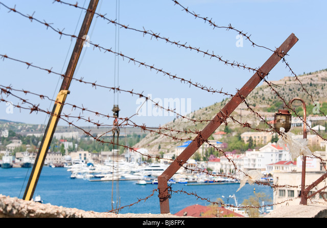Summer view of seafront with ships at pier and barblock in foreground (Balaclava Town, Crimea, Ukraine) - Stock Image