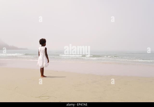 Rear view of african american girl at beach looking out to sea - Stock Image