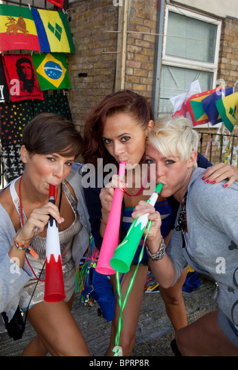 Notting Hill Carnival, three cheeky girls blowing vuvuzelas, London, England, United Kingdom - Stock Image
