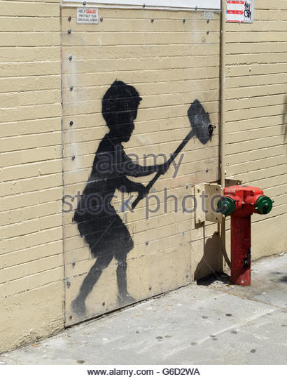 Banksy street graffiti art, 'Hammer Boy',  along sidewalk in NYC, protected by plexiglass - Stock Image