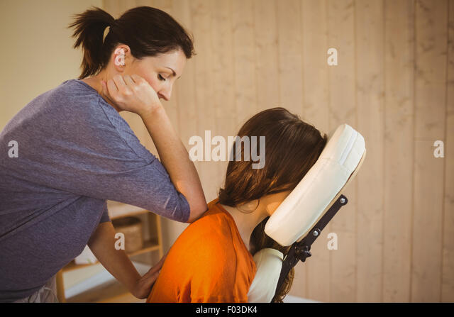 Young woman getting massage in chair - Stock Image