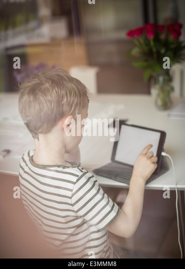 Boy using digital tablet at table - Stock Image