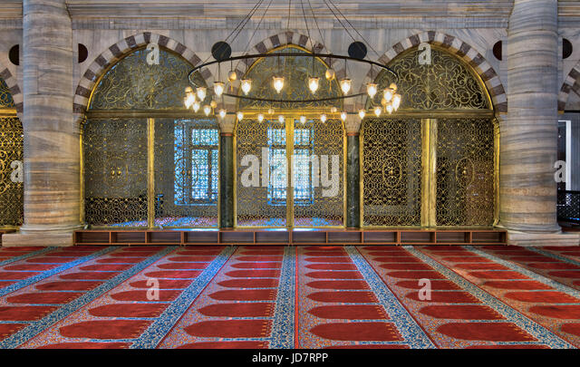 Interior shot of three arched ornate engraved golden doors, big chandelier over marble wall with pillars and red - Stock Image
