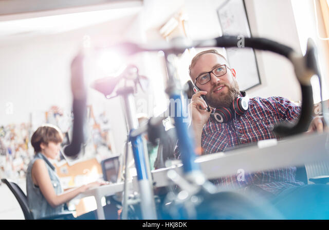 Bicycle leaning against desk next to male design professional talking on cell phone in office - Stock-Bilder
