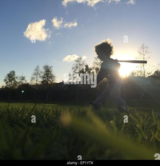 Boy playing with baseball bat - Stock Image