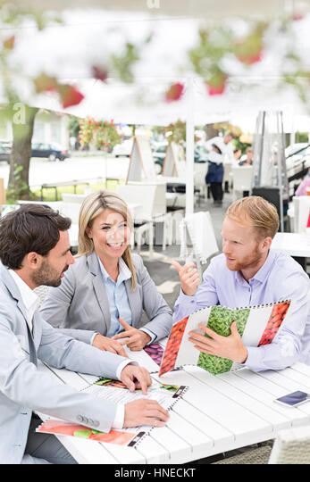Portrait of happy businesswoman with male colleagues deciding menu at sidewalk cafe - Stock Image