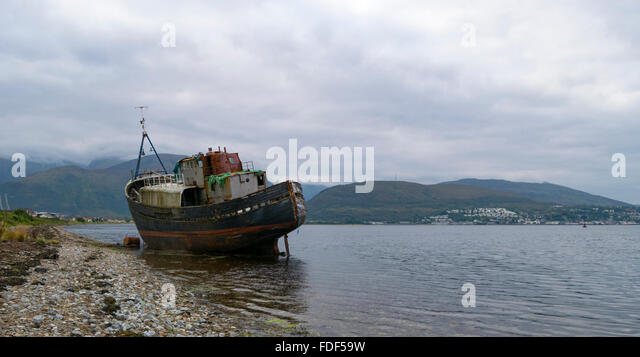 A grounded fishing boat on a beach at Loch Linnhe, with Ben Nevis in the background. Caol, Scotland, UK. - Stock Image