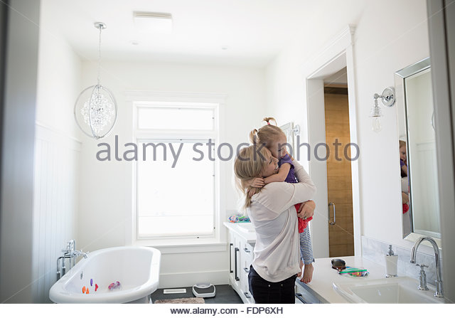 Mother hugging daughter at bathroom counter - Stock Image