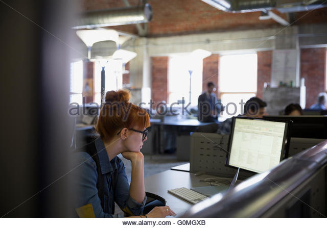 Businesswoman working at computer in office cubicle - Stock Image