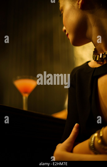 Woman sitting alone at bar with cocktail - Stock Image