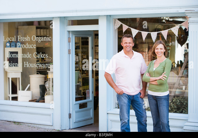 Couple standing in front of organic food store smiling - Stock Image