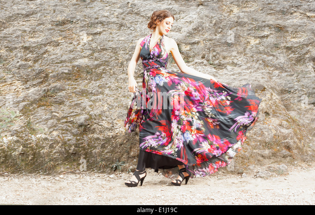 Young woman wearing silk dress with floral design - Stock Image