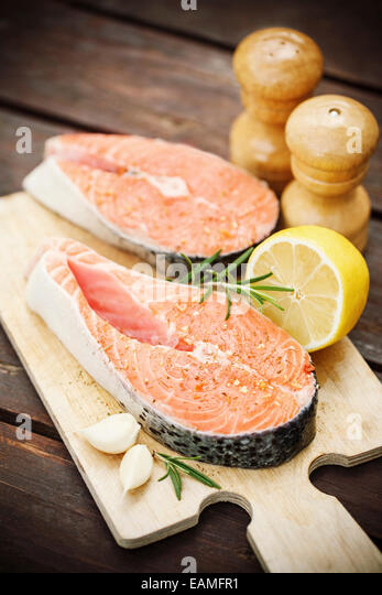 Two fresh salmon steaks with spices and herbs - Stock Image