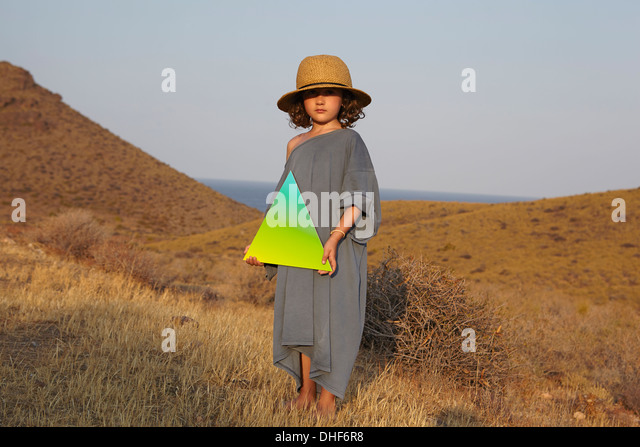 Portrait of girl holding triangle shape in field - Stock Image