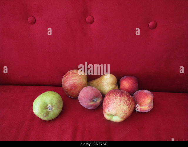 Fruit on red sofa - Stock Image