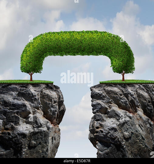 Bridge the gap business concept as two trees on a high steep cliff leaning towards each other bridging together - Stock-Bilder