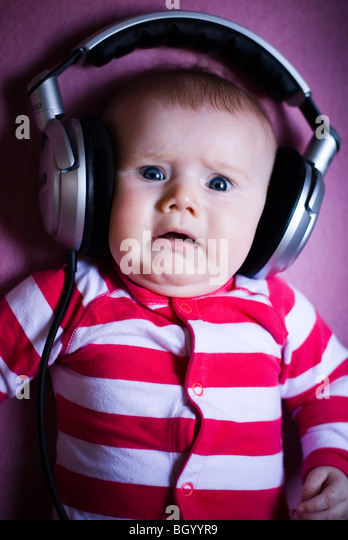 Baby wearing headphones - Stock Image