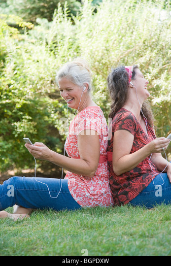 Side profile of two mature women sitting back to back in a park and listening to MP3 players - Stock-Bilder
