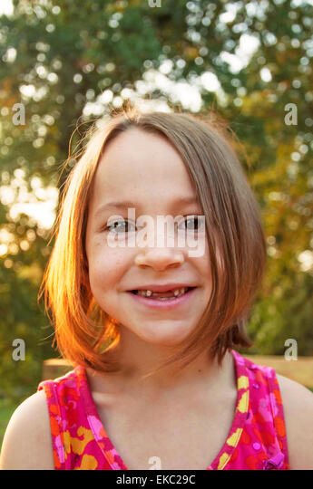 Girl proudly shows missing teeth - Stock Image