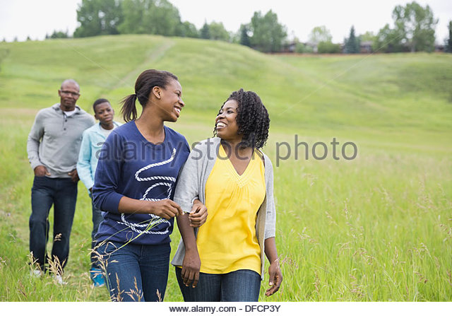 Happy family walking through field - Stock Image