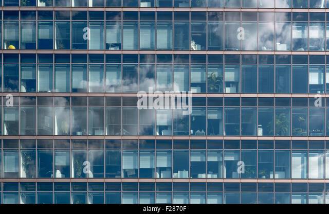 Woken spiegeln sich in der Glasfassade eines Bürohauses - Stock-Bilder