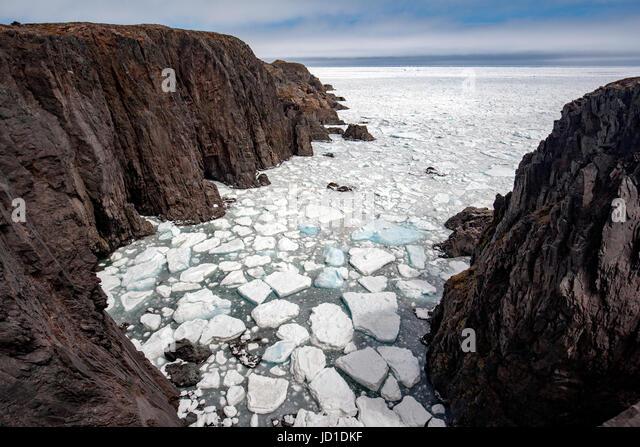 Rugged Coastline, Sea Stacks, and Sea Ice at Spillars Cove, near Bonavista, Cape Bonavista Peninsula, Newfoundland, - Stock Image