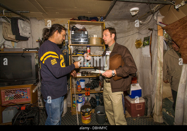 A local minister visits an indigent military veteran in a makeshift shelter among homeless residents - Stock Image