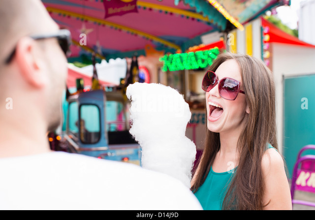 Woman eating cotton candy at fair - Stock Image
