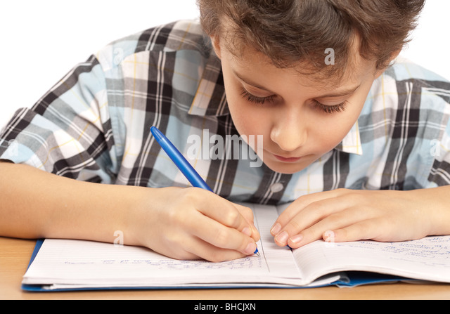 Portrait of a schoolboy doing homework at his desk, isolated on white background - Stock Image