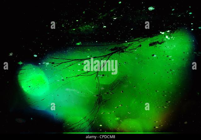 Strange green glowing blob floating in space - Stock Image