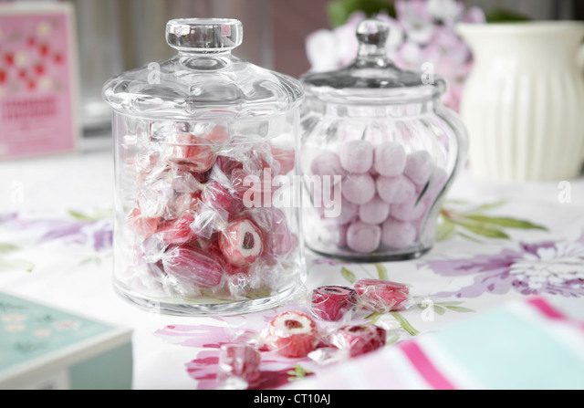 Jars of candies on table - Stock Image