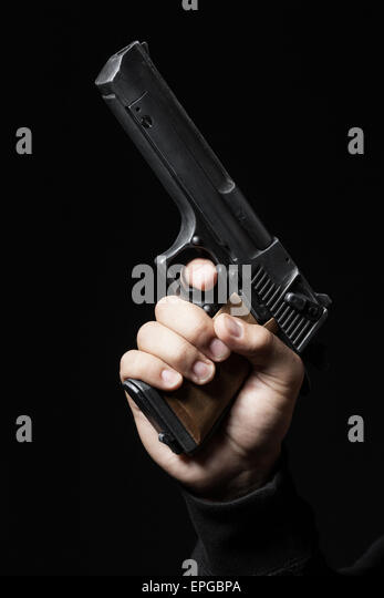 male hand with gun isolated on black background - Stock Image