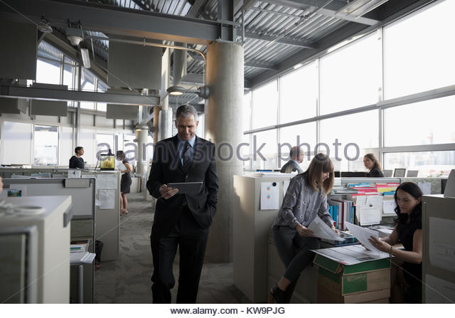 Businessman walking and using digital tablet in open plan office - Stock Image
