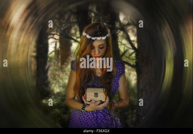 beautiful girl holding a box treasure with a crone in the head in the forest - Stock Image