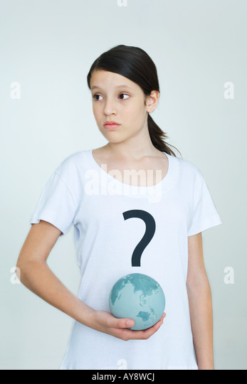 Girl wearing tee-shirt printed with question mark, holding globe, looking away - Stock Image