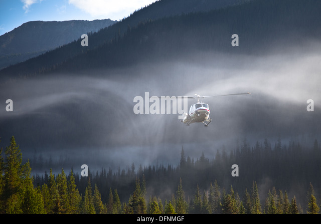 Downdraft from a helicopter rotor is evident in early morning mist - Stock Image