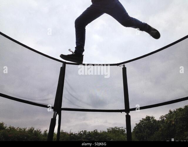 Teenage boy on trampoline almost clearing the net - Stock Image