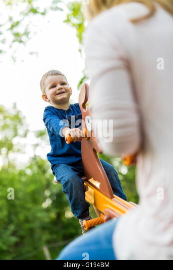 Handsome little boy swinging with his mother - Stock Image