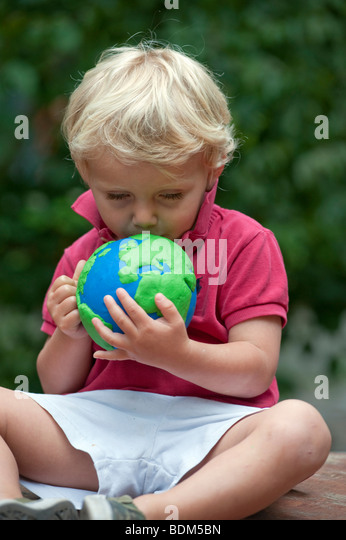 Young boy cuddling and holding a model of planet Earth - Stock Image