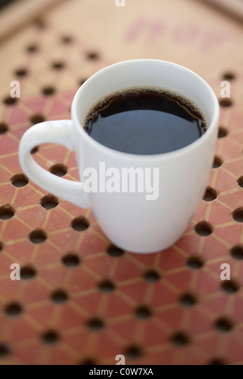 fresh coffee in white cup on game board - Stock Image